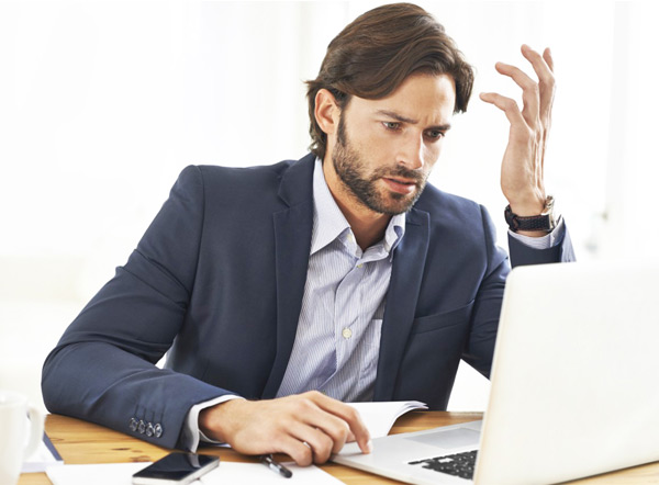 Frustrated Businessman Looking At Laptop
